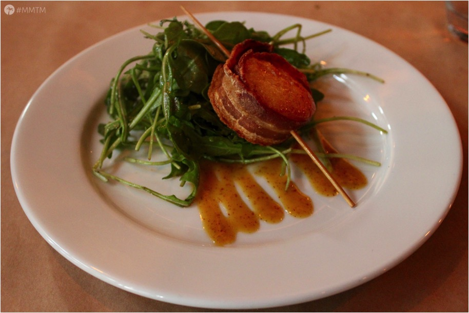 Bacon Wrapped Scallop on arugula with feta and drizzled with orange glaze